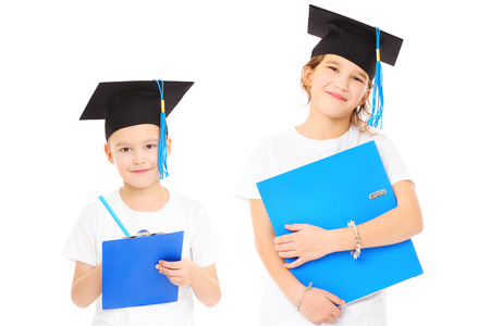 elementary students: A portrait of young siblings in students hat posing over white background