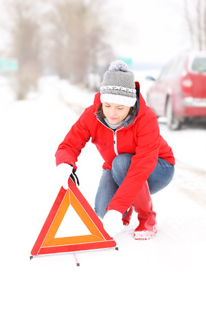 warning triangle: A picture of a young woman having a problem with a car on a winter road