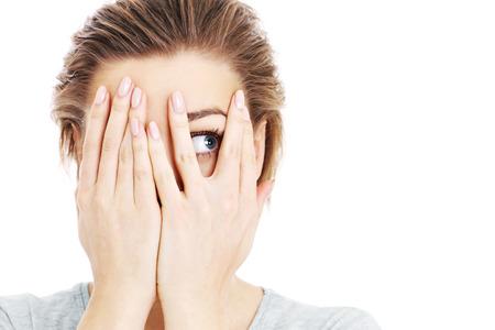 Een foto van een bang vrouw die haar ogen over witte achtergrond Stockfoto