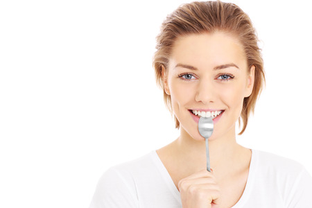 A picture of a young woman posing with a teaspoon over white background