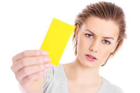 A picture of a serious woman showing a yellow card over white background photo