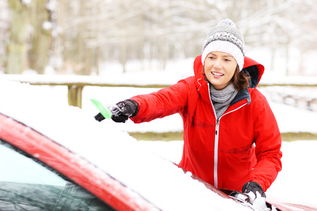 scraping: A picture of a young woman cleaning a windshield from the snow