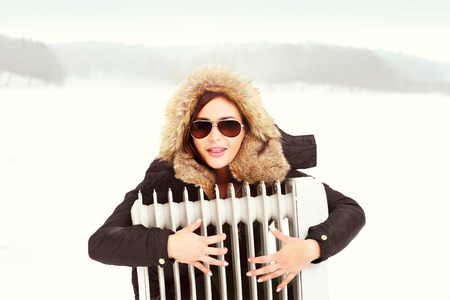 radiator: A picture of a beautiful woman hugging a radiator in winter