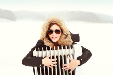radiador: Una imagen de una hermosa mujer abrazando a un radiador en invierno