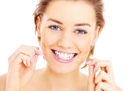 A picture of  beautiful woman flossing her teeth over white background Imagens