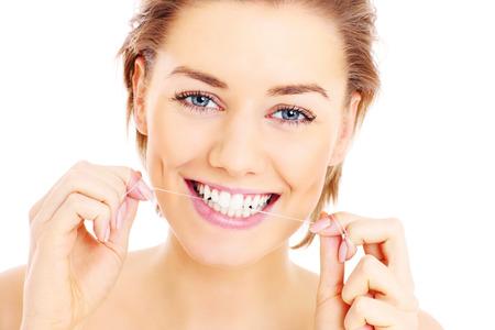 Een foto van mooie vrouw flossen haar tanden over witte achtergrond