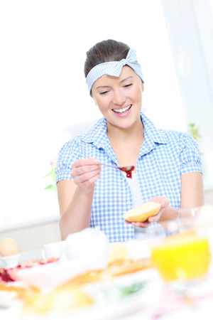 strawberry jam sandwich: A picture of a young woman preparing a strawberry jam sandwich in the kitchen