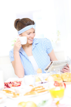 A picture of a young woman eating breakfast and reading a newspaper in the kitchen photo