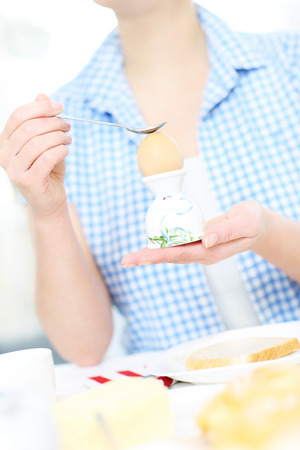 A picture of a woman cracking a hard boiled egg at the table photo