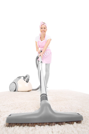 retro housewife: A picture of a retro style housewife vacuumin a carpet over white background Stock Photo