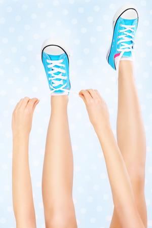 lacing sneakers: A picture of a woman tying her shoe laces over white and blue dotted background Stock Photo