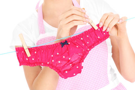 A midsection of a woman hanging up panties over white background