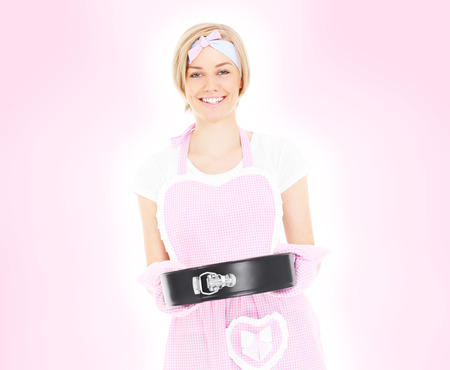 A portrait of a retro style housewife holding a cake tin over pink background photo