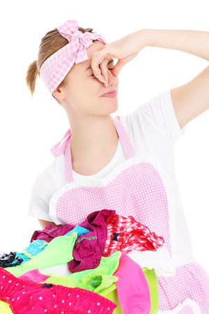 A picture of a young woman holding stinky laundry over white background photo