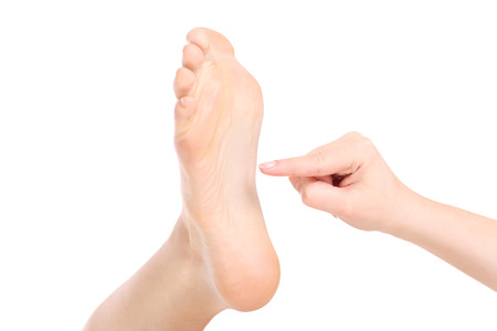 tickling: Apicture of a foot beeing tickled over white background Stock Photo