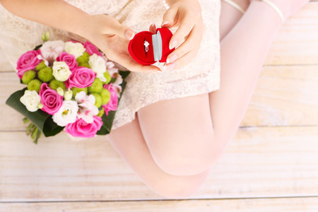 rose ring: A picture of a woman holding engagement ring in a red box over wooden background