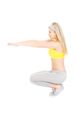 A picture of a young fit woman doing squats over white background photo