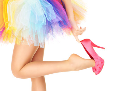 A picture of a woman in a colorful ballerina skirt and pink heels posing over white background photo