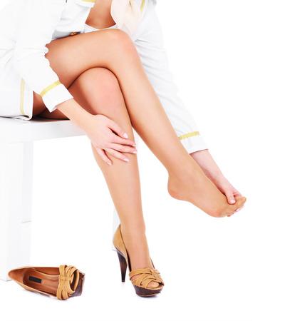 agotado: Una imagen de una mujer con los pies cansados ??sobre el fondo blanco Foto de archivo