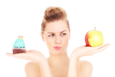 between: A picture of a woman trying to make a decision between cupcake and apple over white background Stock Photo