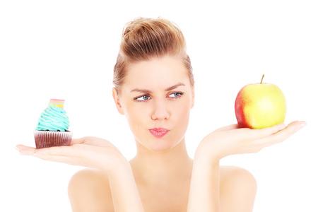 Una foto de una mujer tratando de tomar una decisión entre la magdalena y la manzana sobre fondo blanco Foto de archivo