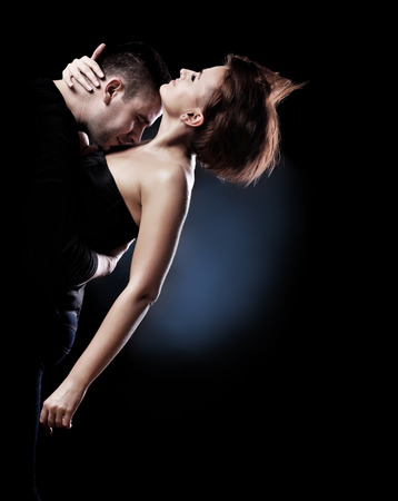 A picture of a young passionate couple dancing over black  Stock Photo