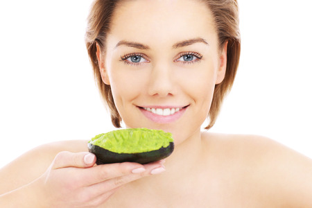 avocados: A portrait of a young woman applying natural avocado mask on her face