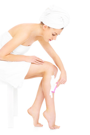 A picture of a young woman shaving her legs over white  photo