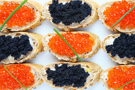 A picture of a plate of black and red caviar sandwiches photo