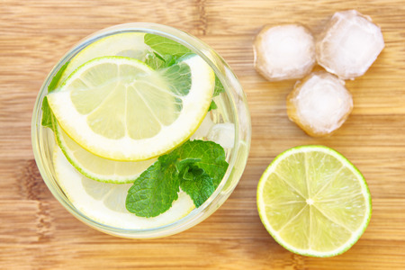 lemonade: A picture of a glass of water with lemon lime and mint served with ice cubes on a wooden board