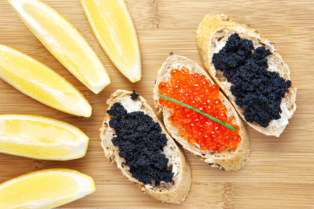 food buffet: A picture of black and red caviar sandwiches served with lemon on a wooden board