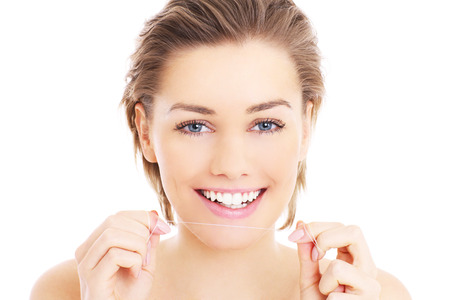 teeth whitening: A picture of beautiful woman using a floss for her teeth over white background Stock Photo