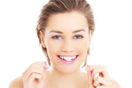Una foto de la hermosa mujer con un hilo dental para los dientes más de fondo blanco
