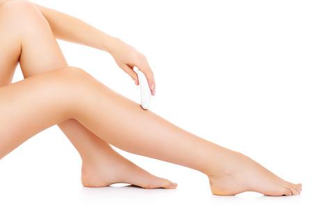 A picture of a young woman depilating her legs over white background