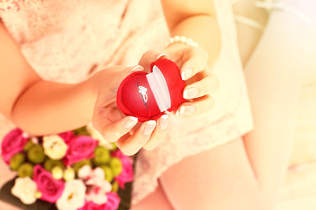 A picture of a woman holding engagement ring in a red box  photo