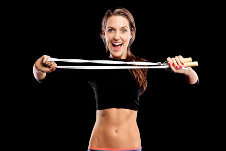 A picture of a fit woman posing with a jumping rope over black background photo