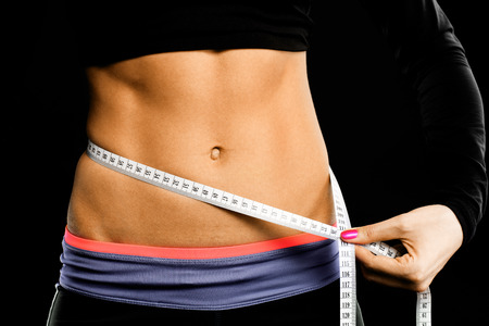A picture of a muscular female belly and tape measure over black background photo