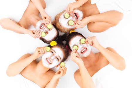 antifaz: Una imagen de cuatro amigos disfrutando de su tiempo en el spa con máscaras faciales sobre fondo blanco Foto de archivo