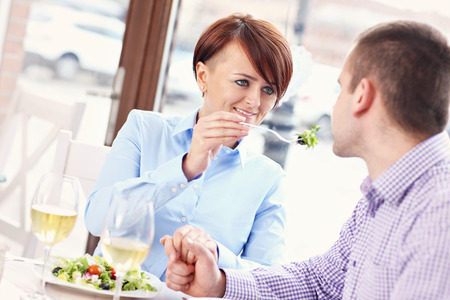 A picture of a young couple sitting in a restaurant and eating photo