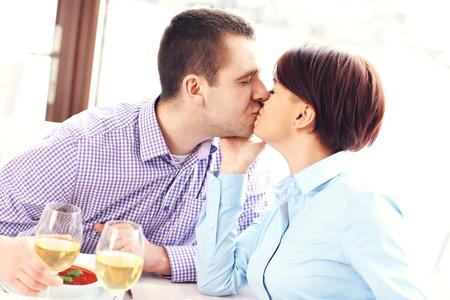 enamorados besandose: Una foto de una joven pareja besándose en un restaurante