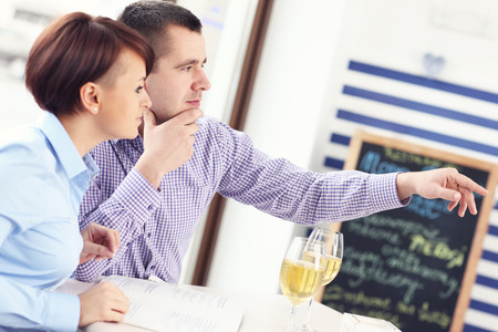A picture of a young couple sitting in a restaurant and pointing at something photo
