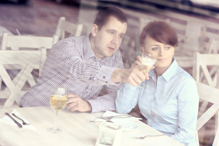 A picture of a young couple sitting in a restaurant and pointing at something the picture taken through the window photo
