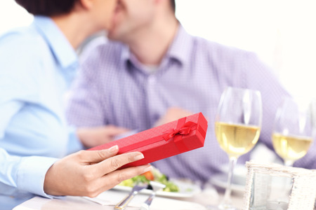 A picture of a beautiful woman getting a present from her husband in a restaurant  photo