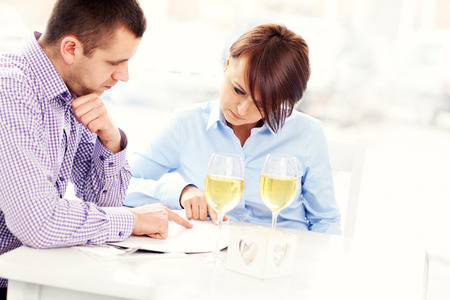 dining out: A picture of a young couple choosing from menu in a restaurant Stock Photo