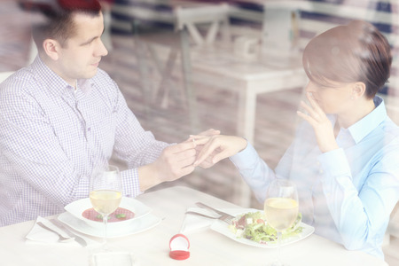 A picture of a beautiful couple getting engaged in a restaurant picture taken through a window photo
