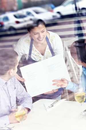 alcohol server: A picture of a young couple sitting in a restaurant and being served