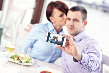 A picture of a young couple taking a picture in a restaurant photo