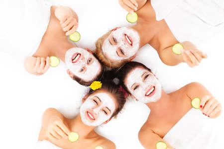 beauty wellness: Een beeld van vier vrienden genieten van hun tijd in kuuroord met gezichtsmaskers op witte achtergrond Stockfoto