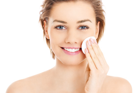 cleanser: A picture of a happy woman cleaning her face with cotton pads over white background Stock Photo
