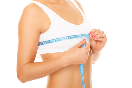 Women measures size of breast over white background Stock Photo